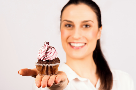 The beautiful young smiling woman is holding a sweet cupcake in her hand and presenting on white background.