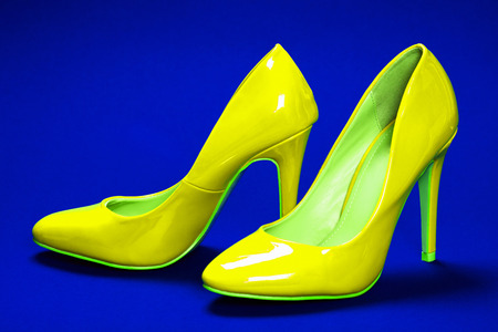 Yellow high heels shoes are on blue background.