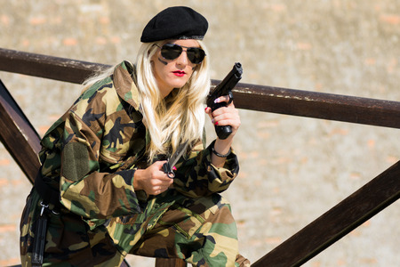 The attractive blond hair woman in military uniform and beret is holding a handgun and knife outdoors. Stock Photo