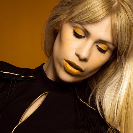 Beauty portrait of beautiful female fashion model with yellow makeup and blond hair.