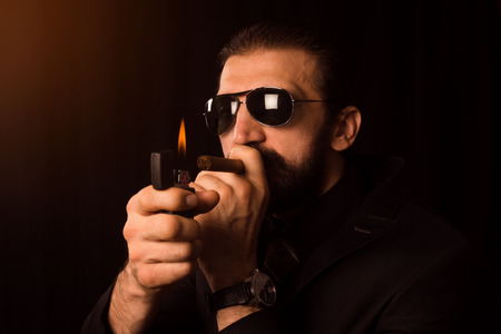 The elegant gentleman with sunglasses is burning his cigar with zippo on black background.