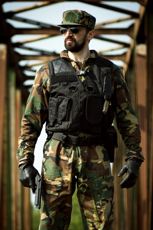 The confident bearded military man is standing with gun in hand outdoors. Stock Photo