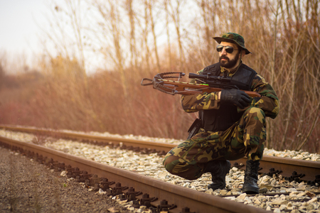 The army soldier in military uniform with crossbow weapon is on railroad track outdoors.
