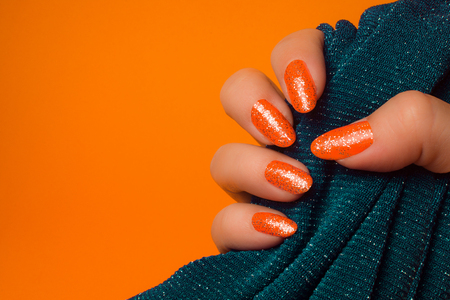 Female hand with glittered orange nails is holding turquoise textile on orange background, manicure and nail care concept.