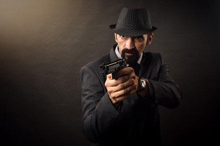 Elegant man in retro style is holding a pistol in hands on dark gray background.
