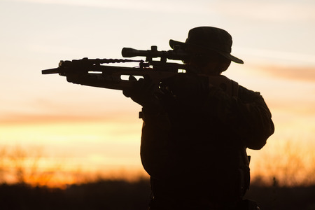 Silhouette of soldier in military uniform with crossbow weapon at sunset light in nature. Stock Photo