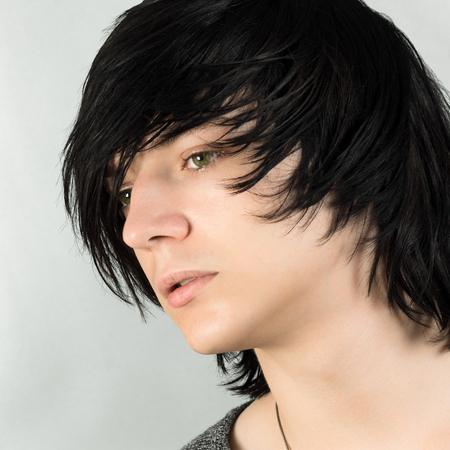 Close-up portrait of handsome teenage boy with black hair emo hairstyle on white background. Imagens