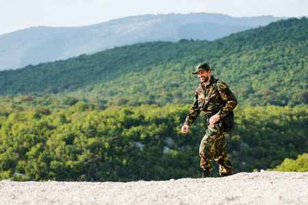 The smiling man in military uniform is walking and enjoying in the nature, adventure and journey concept.