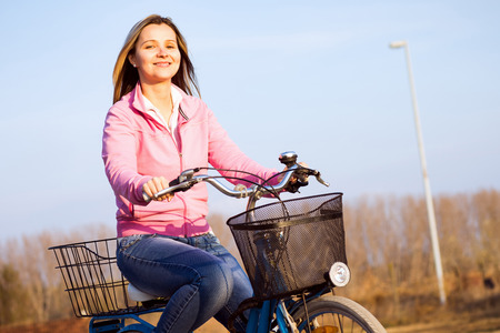 Attractive smiling woman is on bicycle outdoors, active life concept. Imagens