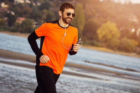The smiling guy in orange sports clothing with earphones and sunglasses is jogging at the riverside, recreation concept.