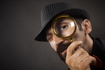 The old-fashioned detective with hat is looking through loupe or magnifier on dark gray background.