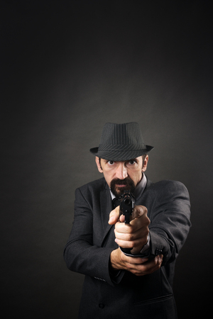 Old-fashioned gangster in suit and hat is aiming with pistol on dark background. Retro and vintage style.