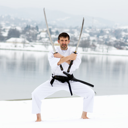 Man in white kimono and black belt is practicing martial arts with two samurai swords barefoot on snow at winter.