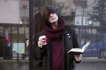 The urban style student boy with book and coffee is standing outdoors at the street and resting.