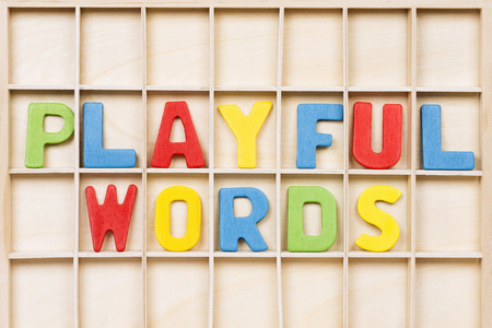 Playful words text from colorful wooden letters are on wooden background, education, learning english or mother language concept.