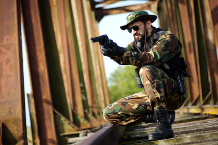 Army soldier in military uniform is aiming with pistol on railway bridge. Stok Fotoğraf