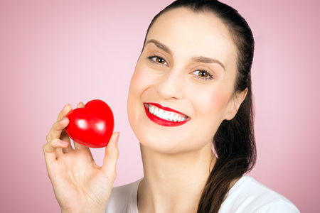 Beautiful smiling woman is holding a little red heart in hand on pink background, love concept. 免版税图像