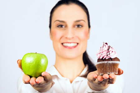 The smiling woman gives a choice to deciding apple or cupcake, healthy or unhealthy eating. Фото со стока