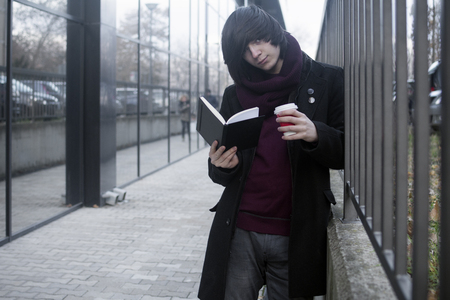 The trendy student is learning, studying, reading a book and drinking coffee at the street.