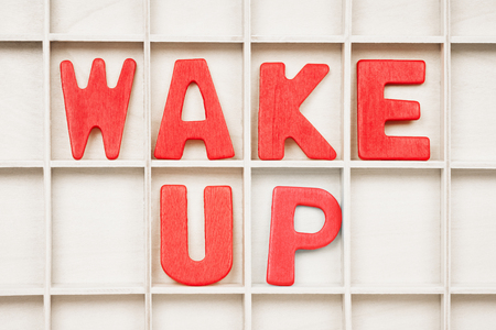 WAKE UP text written by red wooden letters on board, morning or state of mind concept.