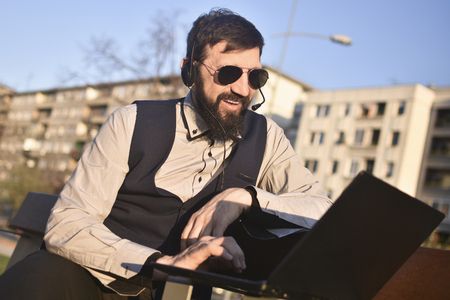 The middle aged bearded smiling man is working at virtual assistent freelance work on his laptop outdoors in city at the street.