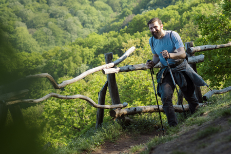 The smiling bearded man is walking with hiking sticks in nature on natural green backgound, active life and adventure concept.
