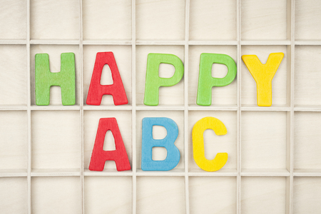 The HAPPY ABC text from colorful wooden letters is on wooden background, learning alphabet.