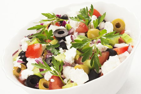 Seasonal colorful Greek salad from different vegetable and feta cheese in white dish on white background.