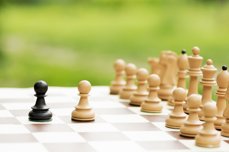 Start or first steps of pawns on chessboard on green background, individuality or conflict concept.