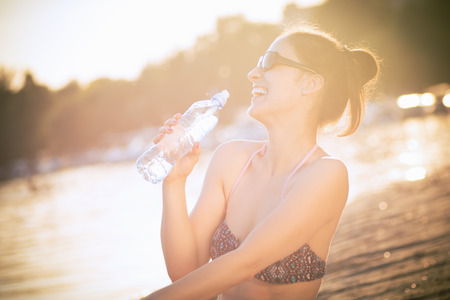 The cheerful laughing woman is drinking water on the beach at summer.
