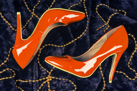Sexy orange high heels shoes are on dark blue fur background with golden pearl jewelry.