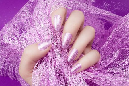 Female hand with glittered pink nails manicure is holding pink decoration on pink background. 写真素材