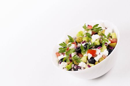 Colorful healthy Greek salad from different vegetables and feta cheese is on white background.