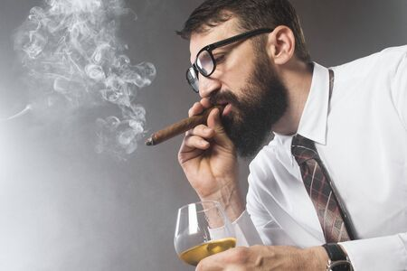The elegant bearded man is smoking cigar and drinking alcohol on gray background.