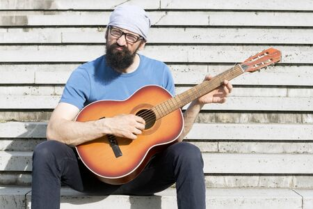 The funny bearded man with grimace is playing guitar and sitting on stairs. 写真素材