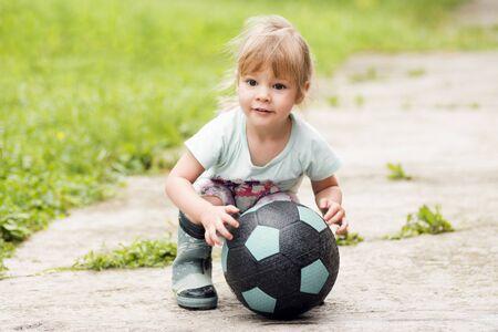 La petite fille mignonne joue avec un ballon de football dans la rue.