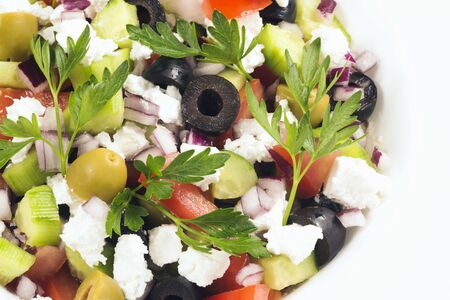 Colorful healthy Greek salad with different vegetables and feta cheese.