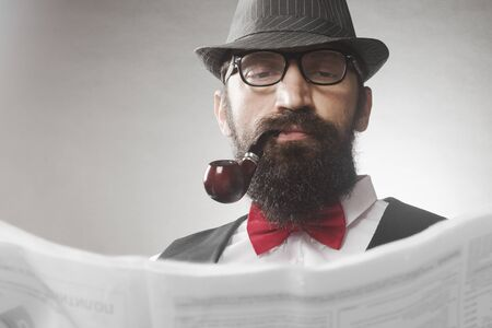 The elegant old-fashioned bearded hipster middle aged man with tobacco pipe is reading newspaper.