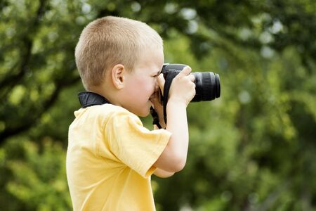 The little blond hair boy photographer is photographing outdoors on green background.
