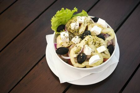 Healthy Greek salad with pepper, olives and feta cheese is on table on brown background.