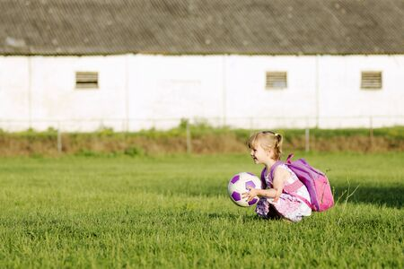 The playful blonde little girl in pink is playing with soccer ball on grass outdoors.
