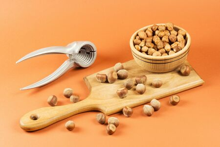 Fresh ripe whole hazelnuts on cutting board and in wooden bowl with nut-cracker on orange background.