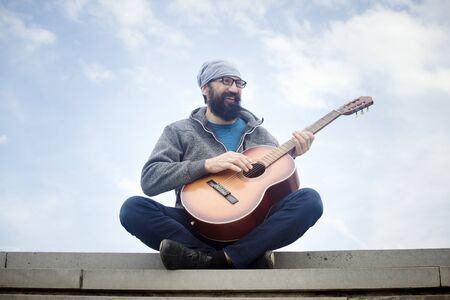 The cheerful bearded man is playing guitar and sitting on the steps outdoors on cloudy sky background. 写真素材