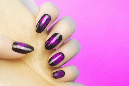 Female hand with pink black nails on pink background, manicure concept.
