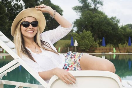 The beautiful smiling woman is relaxing and enjoying at the poolside at summer.