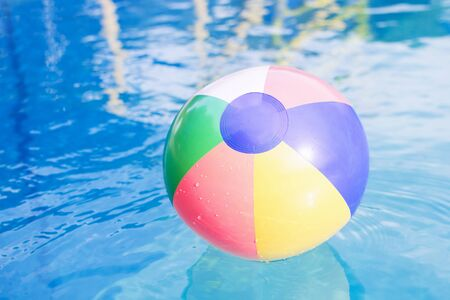The colorful beach ball is on the water in swimming pool at summer.
