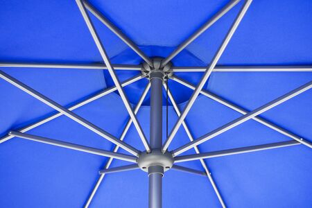 Close-up and geometric shapes of blue parasol or umbrella.