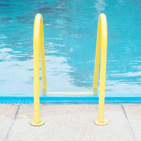 Yellow handrail in the pool for help entering in the water.