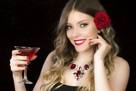 Beautiful young romantic woman is drinking red cocktail on black background. 写真素材