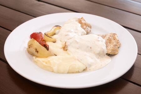 Chicken meat and white bechamel sauce with baked peppers are on white plate on brown table.